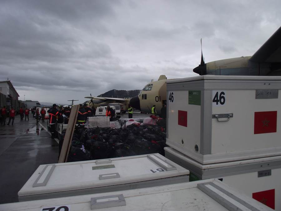 Boxes and bags containing rescue equipment on the tarmac at Bern airport in front of three military aircraft.