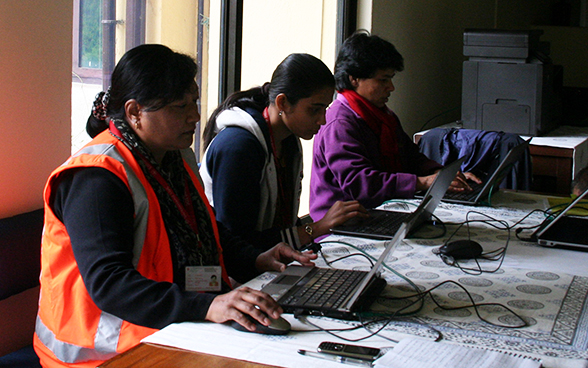 Local staff of the Swiss embassy in Nepal working at a table.