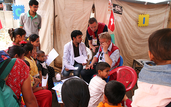 A local doctor and two Swiss aid workers register patients for admission to Gorkha District Hospital.