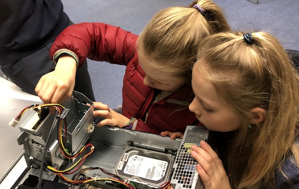 Two girls are handling the inside of a computer.