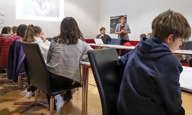 Children listen to a woman presenting the work of the Communications Department of the FDFA Switzerland.